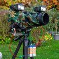 Blitzhalterung am Stativ mit Kamera und Blitzen. Getarnt mit Camouflagestoff